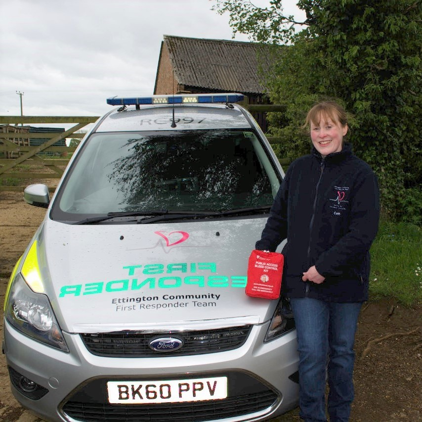 Womsn standing next to an ambulance car