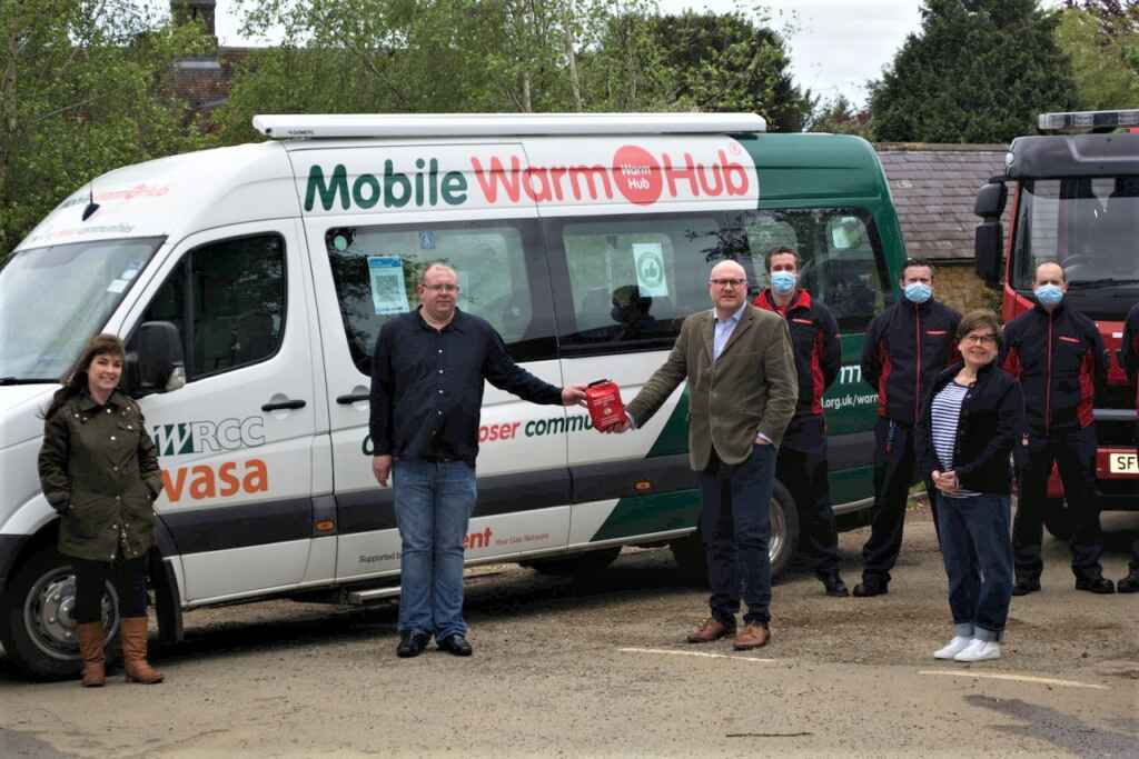 People standing in front of minibus with Mobile Warm Hub lettering and logo