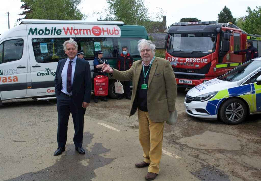 Two men in front of minibus and emergency service vehicles